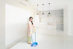 Donna che fa piazza pulita con la scopa immagini stock