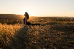 Donna che fa posa ascendente del cane di yoga durante il tramonto Immagini Stock