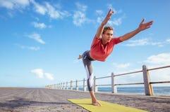 Donna che fa posa di yoga di virabhadrasana alla spiaggia Fotografie Stock
