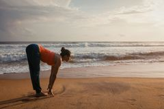Donna che fa saluto Surya Namaskar di Sun di yoga sulla spiaggia immagine stock libera da diritti