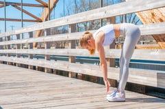Donna che fa scaldarsi ed allungamento del suo corpo prima dell'correre Immagine Stock