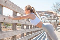 Donna che fa scaldarsi ed allungamento del suo corpo prima dell'correre Fotografie Stock