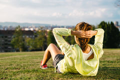 Donna che fa situps e che si esercita nel parco della città Fotografia Stock