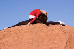 Donna che fa spaccatura sulle rocce Fotografia Stock