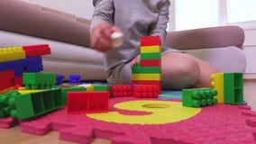 Donna che fa torre dai mattoni del giocattolo archivi video