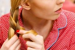 Donna che fa treccia su capelli biondi fotografia stock