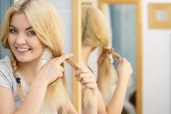 Donna che fa treccia sui capelli biondi fotografia stock