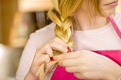 Donna che fa treccia sui capelli biondi immagine stock libera da diritti