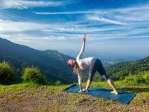 Donna che fa trikonasana di Parivrtta di asana di yoga di Ashtanga Vinyasa Immagini Stock Libere da Diritti