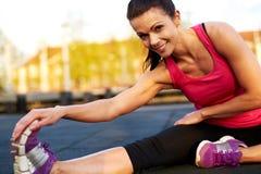 Donna che fa un allungamento messo del tendine del ginocchio che sorride alla macchina fotografica Fotografia Stock Libera da Diritti