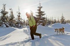 Donna che fa un'escursione con il cane in inverno Fotografia Stock