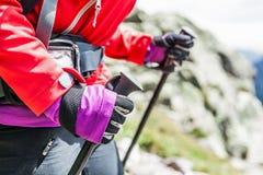 Donna che fa un'escursione con lo zaino in montagne Immagine Stock