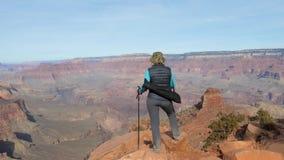 Donna che fa un'escursione in Grand Canyon e negli aumenti le sue mani su da successo archivi video