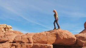Donna che fa un'escursione lungo Ridge Of The Mountain From le rocce rosse del canyon archivi video