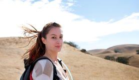 Donna che fa un'escursione mentre esaminando la macchina fotografica Fotografia Stock