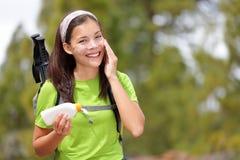 Donna che fa un'escursione mettendo protezione solare Fotografia Stock Libera da Diritti