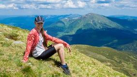 Donna che fa un'escursione in montagne al giorno soleggiato fotografie stock