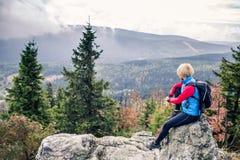 Donna che fa un'escursione in montagne e legno di autunno Immagini Stock