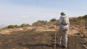 Donna che fa un'escursione su un plateau di pietra di Lava On congelato A Volcano In Africa dormiente stock footage