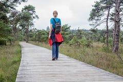 Donna che fa un'escursione sul percorso di legno in natura Fotografia Stock