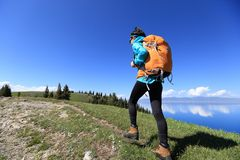 Donna che fa un'escursione sul picco di montagna fotografie stock