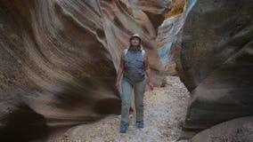 Donna che fa un'escursione sulla gola asciutta del fiume con le rocce liscie ed ondulate del canyon Fotografie Stock Libere da Diritti