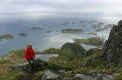 Donna che fa un'escursione vicino a Henningsvaer un giorno piovoso Immagini Stock Libere da Diritti