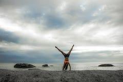 Donna che fa un verticale su una roccia al tramonto sulla spiaggia di Bakovern, Cape Town fotografia stock