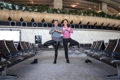 Donna che fa yoga in aeroporto Immagine Stock