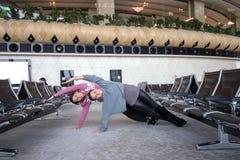 Donna che fa yoga in aeroporto Immagine Stock Libera da Diritti