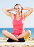 Donna che fa yoga alla spiaggia Immagine Stock