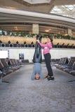 Donna che fa yoga nel corridoio dell'aeroporto Immagine Stock