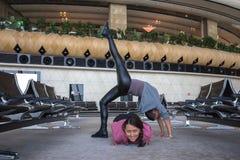 Donna che fa yoga nel corridoio dell'aeroporto Immagine Stock Libera da Diritti