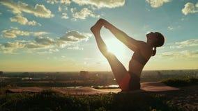Donna che fa yoga nella posa di galleggiamento della barca nel parco al tramonto stock footage