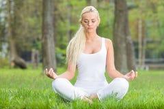 Donna che fa yoga in sosta immagine stock