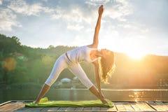 Donna che fa yoga sul lago