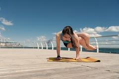 Donna che fa yoga sul pavimento di legno Fotografia Stock