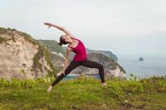 Donna che fa yoga sulla costa della scogliera dell'oceano Fotografia Stock