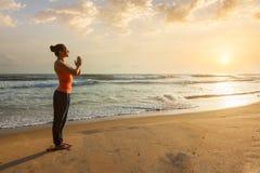 Donna che fa yoga sulla spiaggia fotografia stock