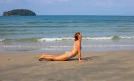 Donna che fa yoga sulla spiaggia di sabbia Attività tropicale di vacanza della spiaggia Ragazza nella posizione di asana Immagine Stock Libera da Diritti