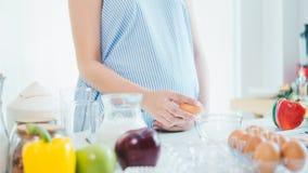 Donna che fende un uovo in una ciotola con fare una pausa nella cucina immagini stock libere da diritti