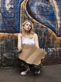Donna che finge di elemosinare contro il muro di mattoni immagine stock