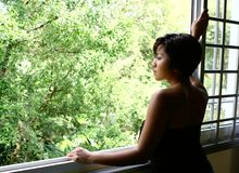 Donna che fissa dalla finestra Fotografia Stock Libera da Diritti