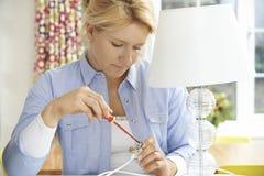 Donna che fissa spina elettrica sulla lampada a casa Immagini Stock Libere da Diritti