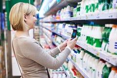 Donna che fotografa con l'etichetta dello smartphone dei prodotti lattier-caseario Fotografia Stock