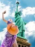 Donna che fotografa la statua della libertà Fotografia Stock