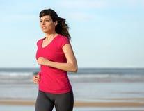 Donna che risolve sulla spiaggia immagini stock
