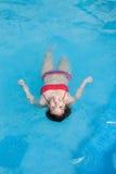 Donna che galleggia nello stagno Immagine Stock Libera da Diritti