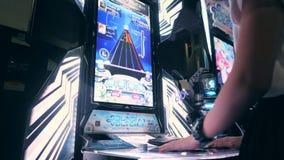 Donna che gioca Arcade Machine Game e che spinge regolatore intelligente Buttons 4K Zona del gioco nel centro commerciale di MBK  stock footage
