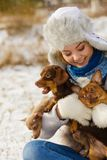 Donna che gioca con i cani durante l'inverno immagini stock libere da diritti